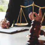 scales of justice with writing hand in background